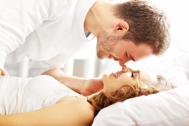 Foto di una giovane coppia che si bacia a letto