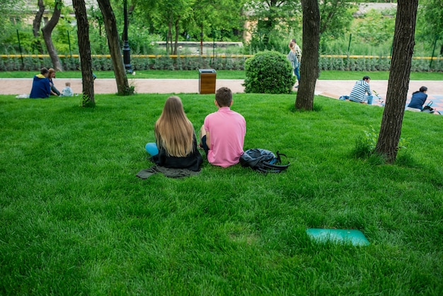 Una foto di una giovane coppia felice che utilizza gli smartphone nel parco. torna indietro foto