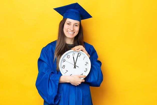 Una foto di una giovane donna felice che tiene un grande orologio bianco vestita in uniforme blu di laurea