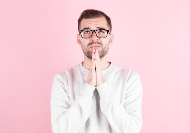 Foto di giovane uomo isolato su rosa, dopo aver unito le mani in preghiera, desiderando sognare e aspettando il meglio