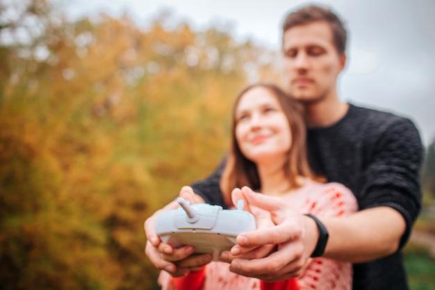 Foto di giovane uomo e donna in piedi insieme e tenendo il telecomando da drone