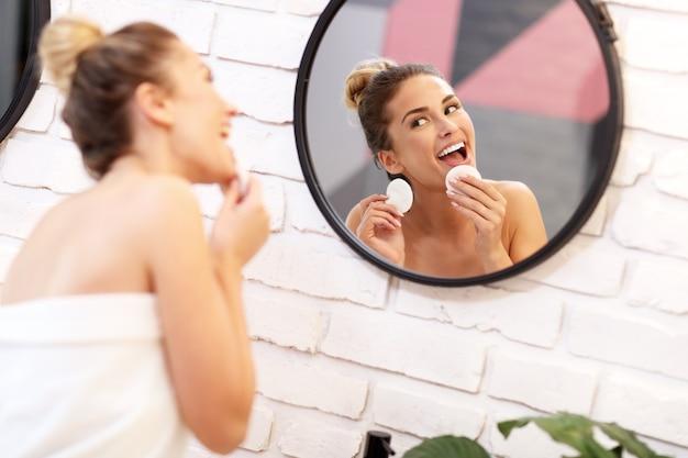 Immagine di una giovane donna che pulisce il viso nello specchio del bagno