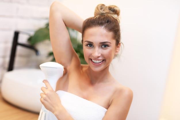 Immagine di una giovane donna che rimuove i peli dalle ascelle in bagno