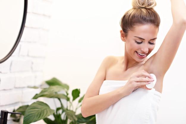 Immagine di una giovane donna che usa il deodorante in bagno