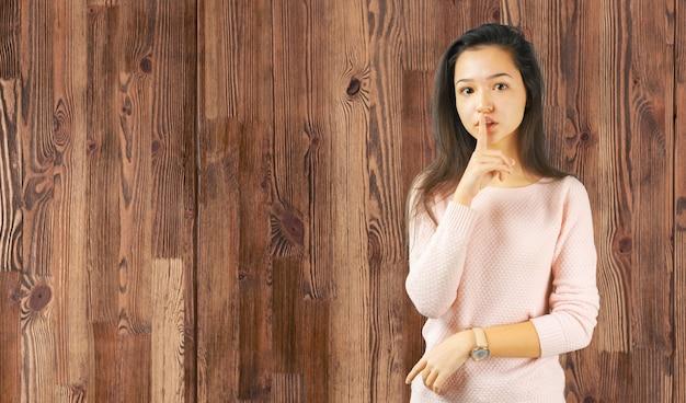 Foto di una giovane donna con un dito sulle labbra che fa segno di calma