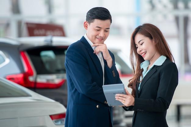 Immagini di clienti asiatici e venditori felici che acquistano auto nuove che stipulano accordi di vendita con concessionari presso rivenditori di auto.