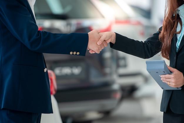 Immagini di clienti e venditori asiatici mano nella mano felici di acquistare nuove auto che fanno accordi di vendita con i concessionari di auto presso i rivenditori di auto.