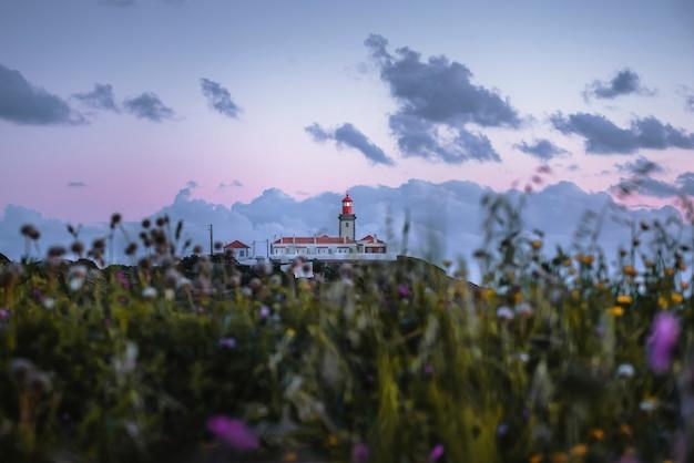 Paesaggio pittoresco con un faro al tramonto a sintra portogallo