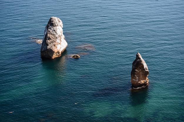 Una pittoresca grande pietra si erge su tutti i lati circondata da un paesaggio marino d'acqua