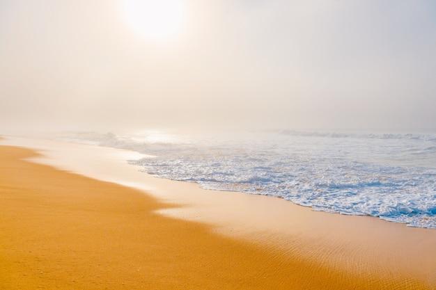 Vista sul mare scenica pittoresca con la spiaggia nebbiosa.