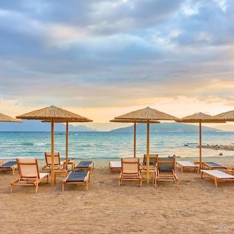 Vista pittoresca della spiaggia con file di ombrelloni di paglia in riva al mare al tramonto