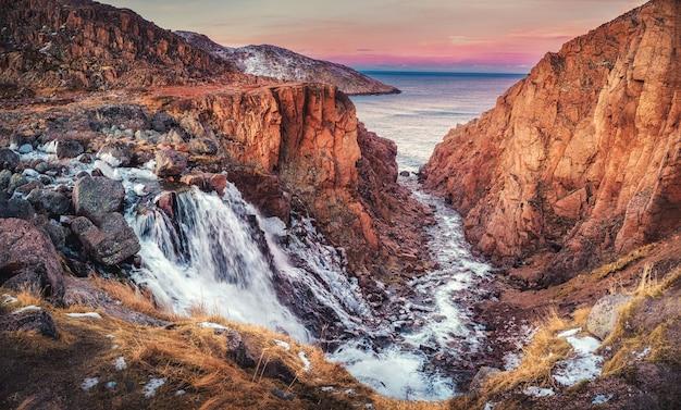 Pittoresca cascata del piccolo lago della batteria sulla penisola di kola, teriberka. russia.