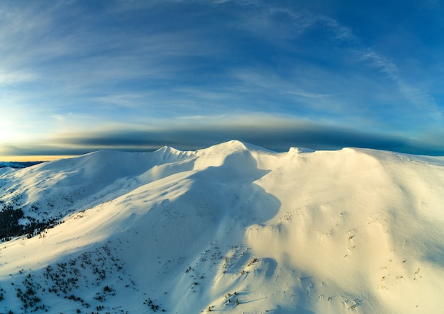 Pittoresco panorama invernale di colline di montagna ricoperte di neve e abeti in una giornata soleggiata e limpida con il sole e il cielo blu