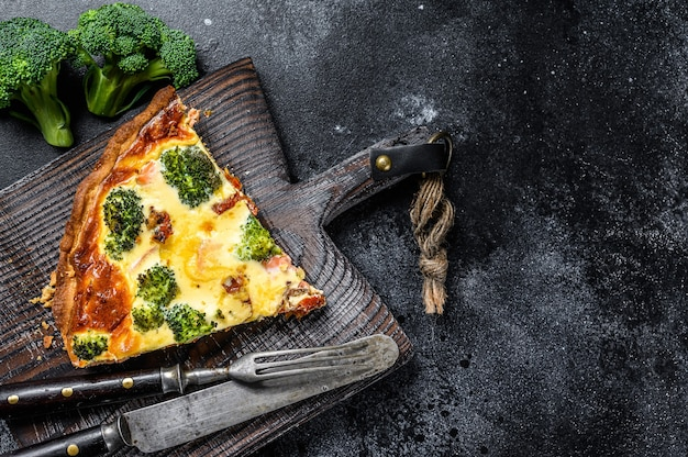 Torta quiche con salmone pesce rosso e broccoli. sfondo nero. vista dall'alto. copia spazio.