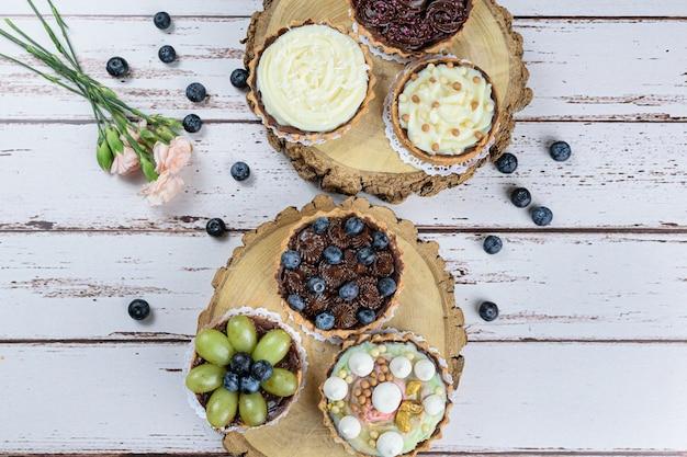 Torta con pasta burrosa farcita con ganache al cioccolato, decorata con mertilos. su un piatto di legno e circondato da altre torte e rose.
