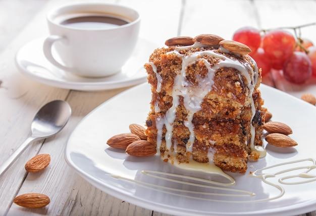 Torta con caramello, salsa al latte bianco e mandorle su un piatto bianco su un fondo di legno bianco