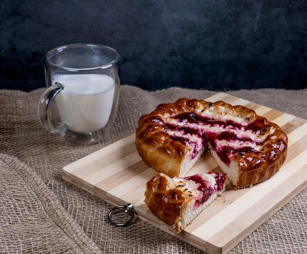 Torta con ciliegie e ricotta su una tavola di legno tagliata un pezzo e una tazza di latte sullo sfondo della tela da imballaggio.