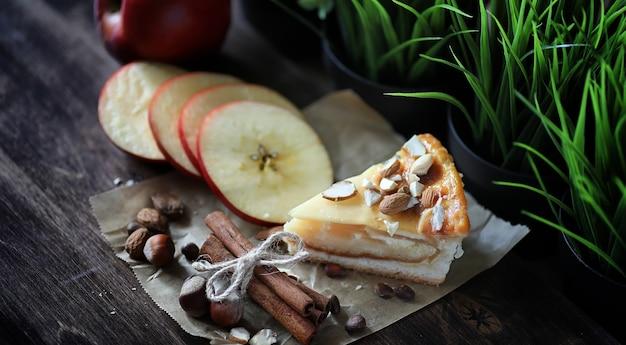 Torta con cannella e mele su un tavolo di legno. pasta fresca con bastoncini di cannella con noci e zucchero a velo. panino con noci e cannella sul tavolo.