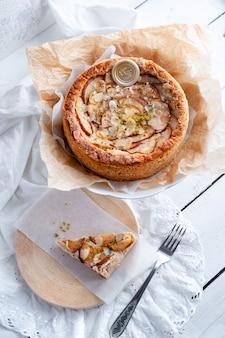 Torta con formaggio blu dor, pere e mandorle, tutto il giro su un piatto su un tavolo bianco
