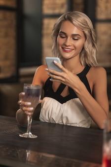 Pezzo d'arte. bella donna bionda seduta al bancone del bar e scattare una foto del suo cocktail mentre sorride
