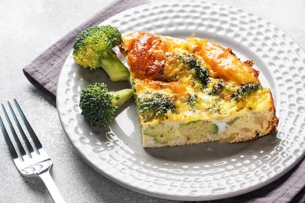 Frittata al forno pezzo con broccoli su un piatto. tavolo in cemento piatto di dieta sana.