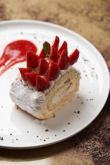 Un pezzo di rotolo di biscotti con panna e fragole. rotolo di torta con fragole fresche sul piatto bianco. dessert del ristorante di lusso