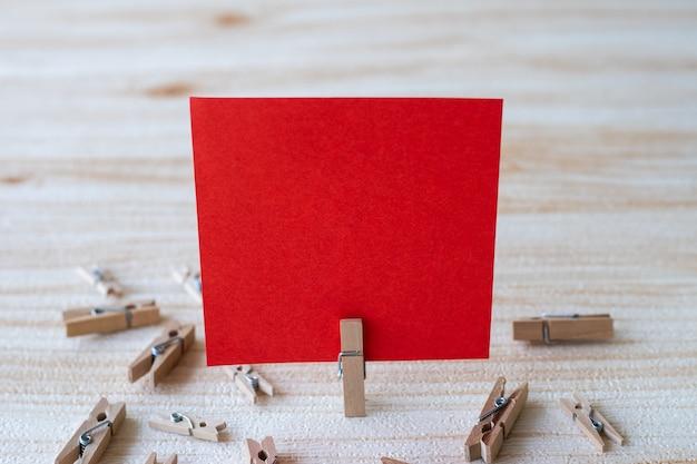 Pezzo di nota quadrata vuota circondata da fermagli per bucato che mostrano un nuovo significato di carta adesiva vuota