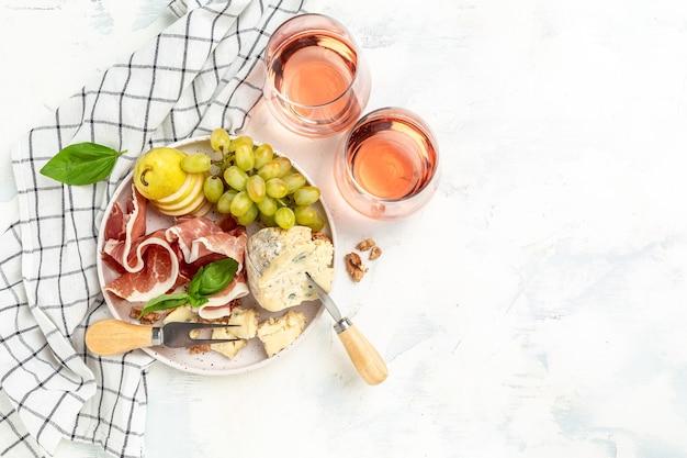 Pezzo di formaggio blu noci e miele, prosciutto con uva vibrante, vino rosato, coltello da formaggio, forchette, noci e miele, concetto di celebrazione della festa. posto per il testo, vista dall'alto.