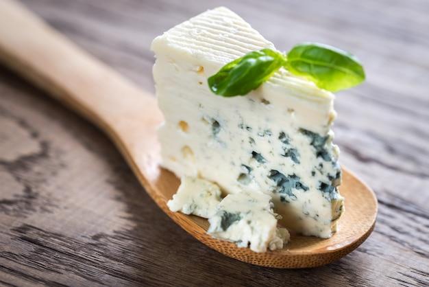 Pezzo di formaggio blu sul cucchiaio di legno