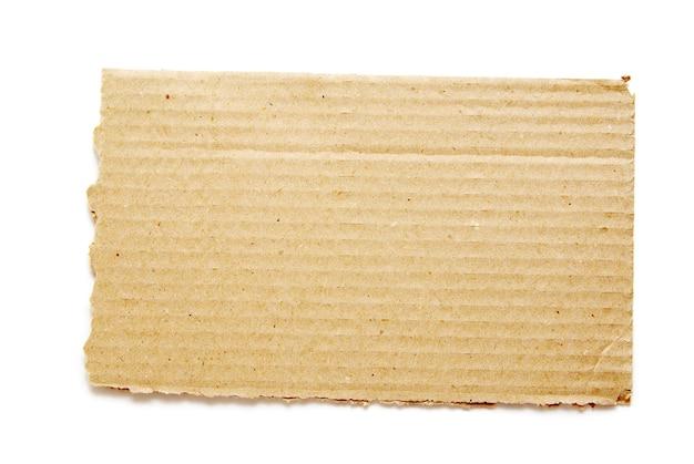Pezzo di cartone ondulato marrone su bianco