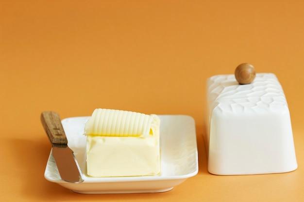 Un pezzo di burro in un piatto di burro e un coltello su uno sfondo colorato. messa a fuoco selettiva.