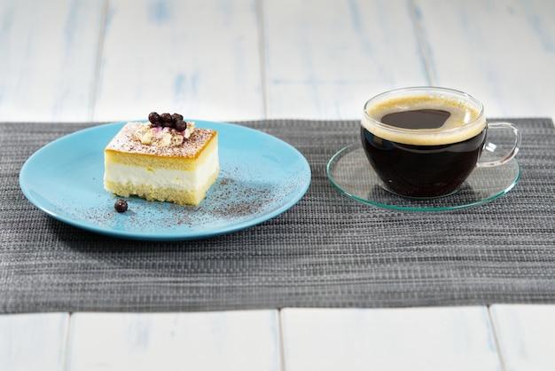 Un pezzo di torta su un piatto blu e una tazza di caffè