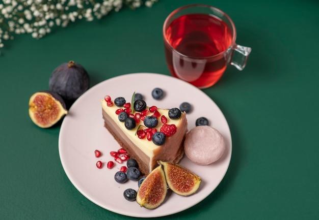 Un pezzo di torta su un piatto rosa con frutti di bosco freschi e amaretti una tazza di tè su verde scuro