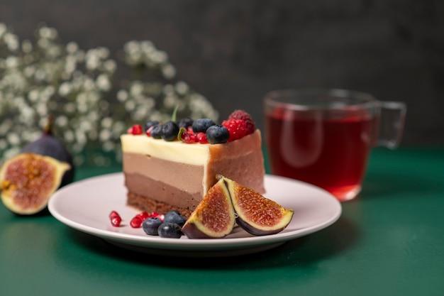 Un pezzo di torta su un piatto rosa con frutti di bosco freschi e una tazza di tè nelle vicinanze su un verde scuro