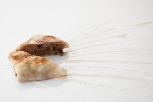 Un pezzo di torta versato con salsa dolce su sfondo bianco