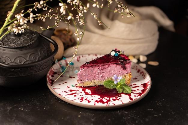 Pezzo di torta. dessert ai lamponi con salsa ai frutti di bosco, marmellata, fiori freschi e foglie di menta. natura morta con torta e teiera