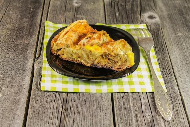 Un pezzo di torta su un piattino su un tavolo di legno