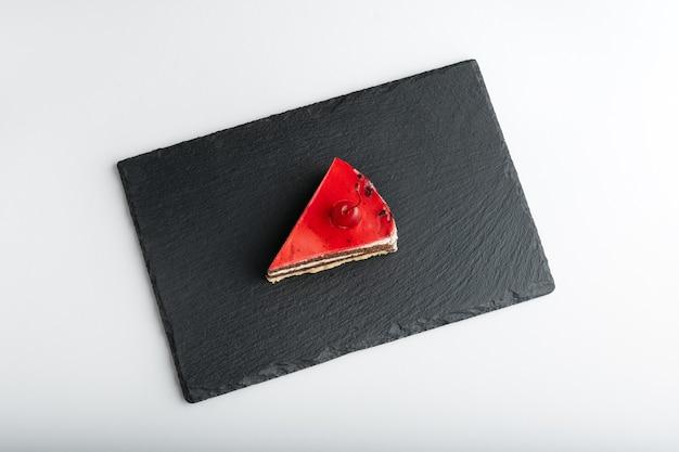Pezzo di torta con la ciliegia su un basamento di pietra grigia su fondo bianco. vista dall'alto.