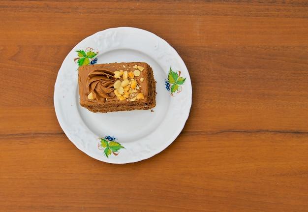 Pezzo di torta con i dadi sul piatto sulla tavola di legno. vista dall'alto