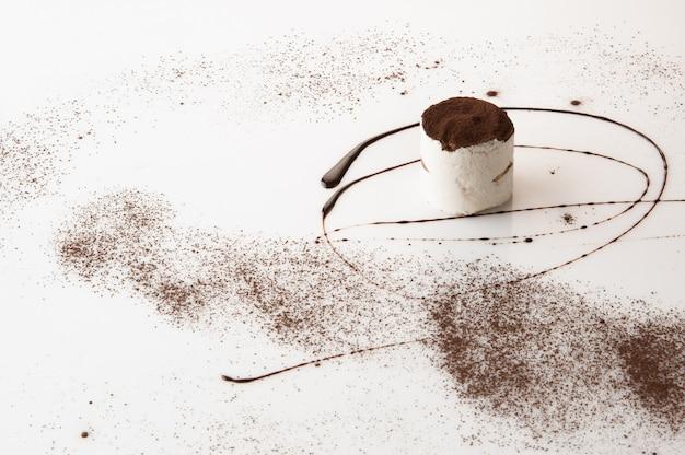 Un pezzo di torta con cosparso di zucchero a velo su uno sfondo bianco
