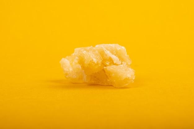Un pezzo di cera di cannabis su sfondo giallo.