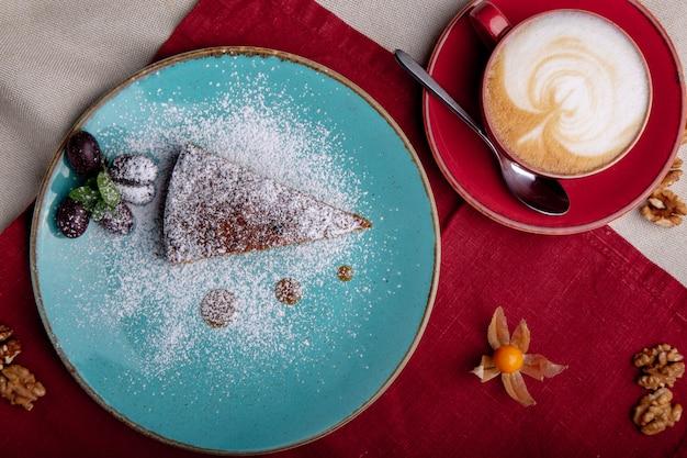 Pezzo di torta di carote ricoperta di zucchero a velo su un piatto blu Foto Premium