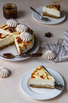 Pezzo di cheesecake alla vaniglia di carote con topping al caramello salato e meringa su un piatto in ceramica bianca
