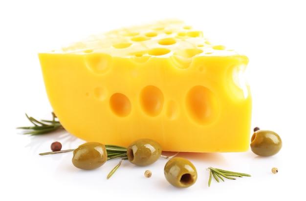Pezzo di formaggio con olive verdi, isolato su bianco