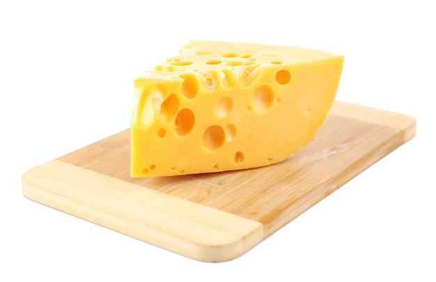 Pezzo di formaggio sulla tavola di legno, isolato su bianco