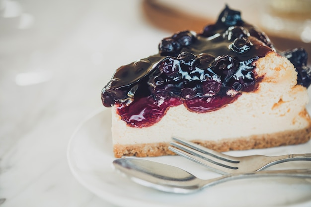 Pezzo di cheesecake con salsa di mirtilli sul piatto bianco. Foto Premium