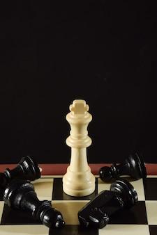 Su un pezzo di una scacchiera c'è una figura re e intorno ad essa giacciono i pezzi neri sconfitti da esso