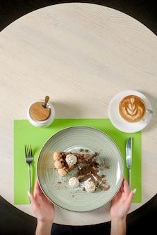 Un pezzo di torta al cioccolato decorata con meringhe, chicchi di caffè e briciole di biscotti, cappuccino. dessert tiramisù, vista dall'alto.