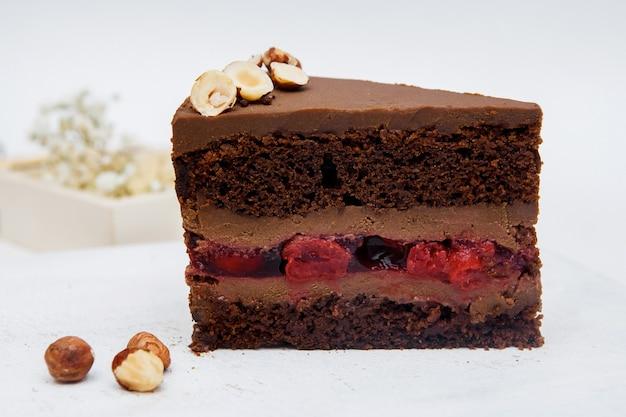 Un pezzo di torta al cioccolato con ciliegie e nocciole su sfondo bianco