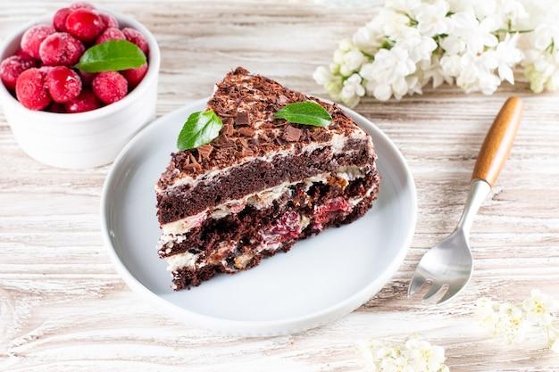 Un pezzo di torta al cioccolato con ciliegia sul piatto su fondo in legno chiaro